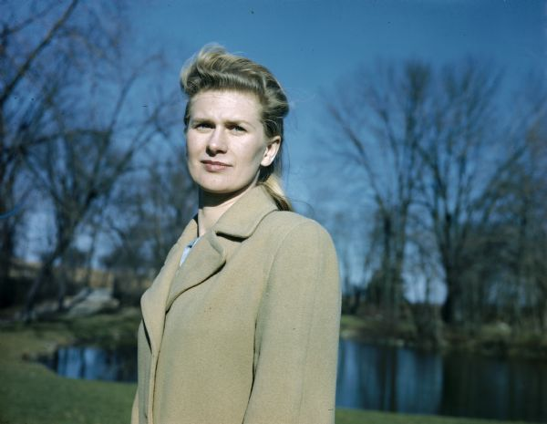 Waist-up portrait of Bernice Boyum Bergner, Sid Boyum's sister, wearing a beige coat. In the background are trees and a pond.