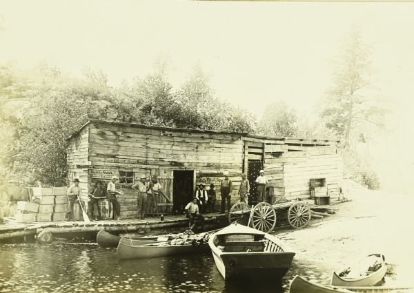 View across water towards the Gang standing in front of G. Swenson's Store in Kettle Falls, which is partially on the water. The steamer schedule is handwritten on left side of front of building. A boat and canoes are at the shore and there is a wagon parked near the store.