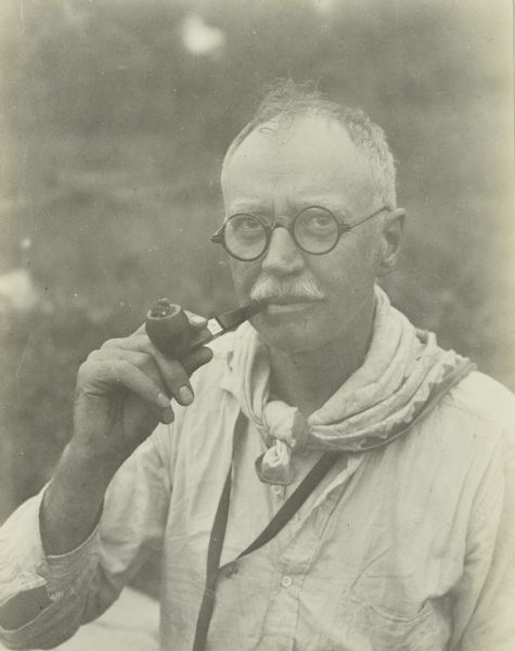 A candid portrait (possibly a self-portrait) of Howard Greene, who is known to The Gang as Dad. He is wearing eyeglasses and is smoking a pipe.