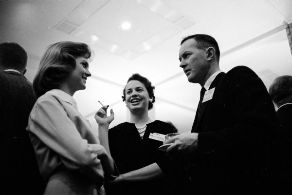 A pair of female University of Wisconsin students speaking with Assemblyman Michael J. Barron (D-Milwaukee) during a reception and banquet for state legislators at the Memorial Union. The girls are Pat Hovey, left, of Birmingham, Michigan and Kitty McGinnis, Milwaukee, Wisconsin.