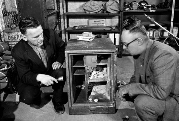 Safe robbers escaped with $1,000 in cash, $2,000 in checks, and several wrist watches when they stole a large safe from the Holmes Tire and Supply Company on Syene Road. Captain Earl Sorenson, left, and Undersheriff Jack Leslie are searching for fingerprints and tool marks on the stolen safe which was found empty later in the day.