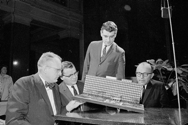 Harold Ames, sitting at center, looking over a model of the State Office building planned for the Hill Farms which was part of the honor awards exhibit of Wisconsin architecture at the State Capitol. Looking on are three Madison winners: Carl Gausewitz (left), Robert Cashin (standing), and Charles Woehrl (right).