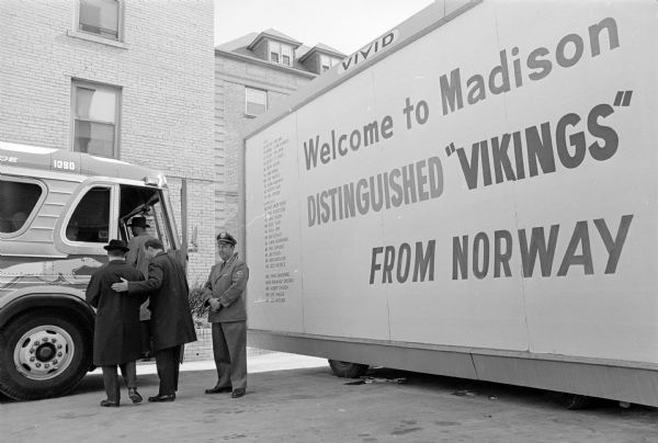 A Scandinavian trade delegation of 25 Norwegian businessmen and journalists visit Madison to publicize the inaugural flight of Scandinavian Airlines System (SAS) direct service from Copenhagen to Chicago. Erik Himle is shown ushering fellow Norwegians onto a sight-seeing bus at the Edgewater Hotel on Wisconsin Avenue.