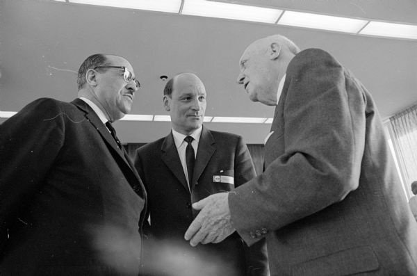 Scandinavian trade delegation of 25 Norwegian businessmen and journalists visit Madison to publicize the inaugural flight of Scandinavian Airlines System (SAS) direct service from Copenhagen to Chicago. Shown (L-R) are delegates Clifton Wharton, and Erik Himle talking to E.B. Fred, UW President.