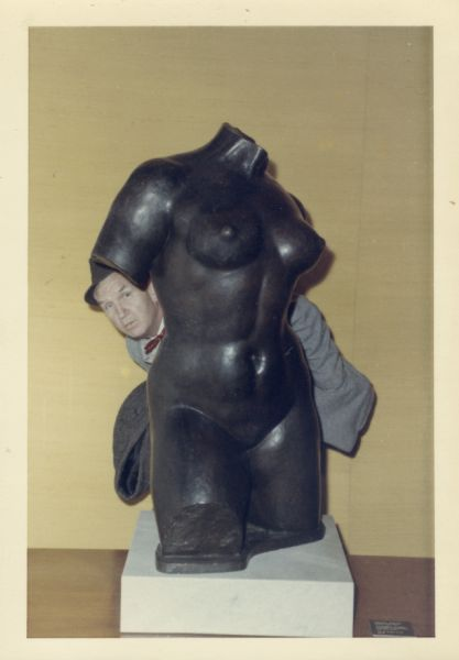 Sid Boyum playfully poking his head out from behind a sculpture of a woman's torso.