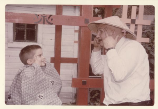 Eric Coffman and Sid Boyum making faces at each other in Sid's backyard at 237 Waubesa Street. Eric is wearing a Kimono and Sid is wearing a conical straw hat.