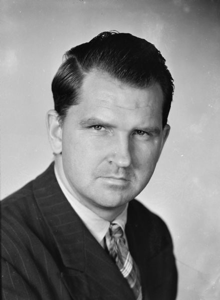 Head and shoulders studio portrait of Sid wearing a suit and tie.