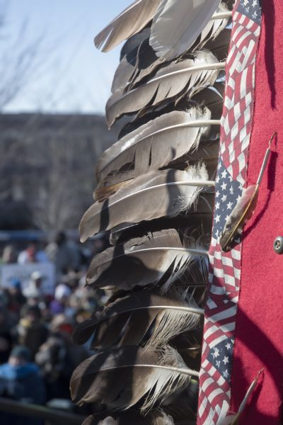 Save the Mounds demonstration around the Capitol Square against Assembly Bill 620. Close-up of feathers attached to what may be a banner. In the background, out of focus, is the crowd attending the demonstration.
