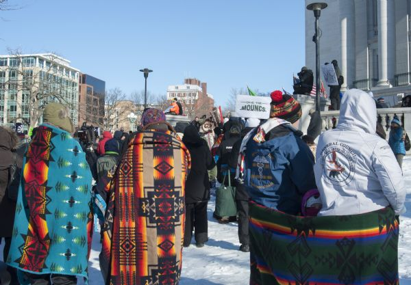 Save the Mounds demonstration around the Capitol building against Assembly Bill 620. Three blankets displaying Native American designs are being used to keep warm.