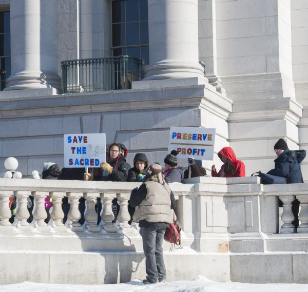 "Save the Mounds demonstration around the Capitol building against Assembly Bill 620. Two demonstrators hold signs that read, ""Save the Sacred"" and ""Preserve over Profit."""