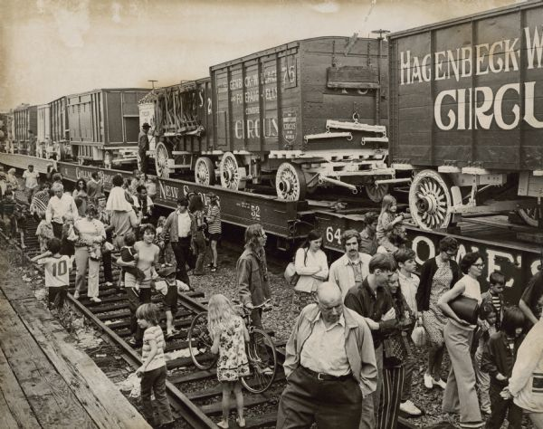 Slightly elevated view of crowd on railroad tracks near flatbed railroad cars carrying circus wagons for a parade.