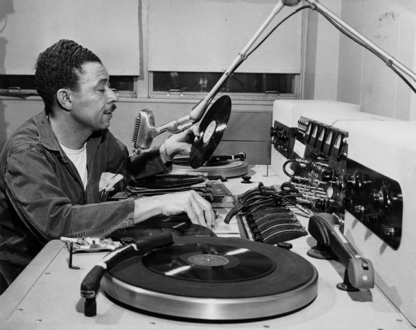 Alvin Benson playing records to broadcast over the radio at the VA Hospital.