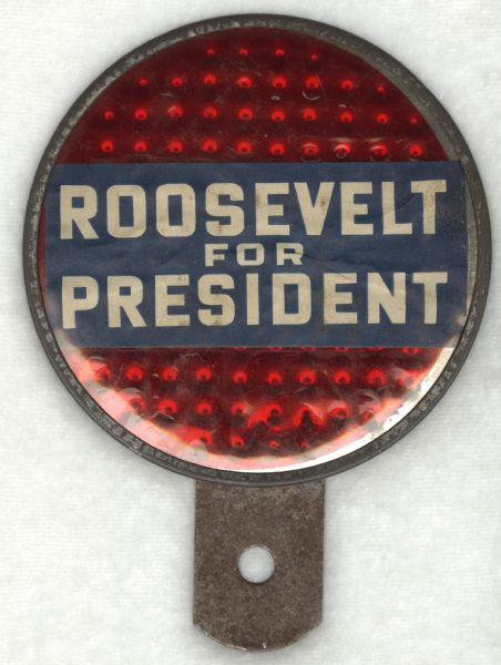 "A round metal reflector with attached tab for mounting. The front has a red, reflective surface with a sign that reads: ""Roosevelt for President."""