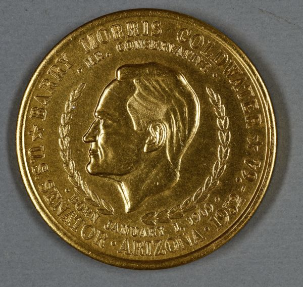 "Coin depicting Barry Goldwater's head in profile surrounded by a laurel wreath, and the words: ""Barry Morris Goldwater, Mr. Conservative, Born January 1, 1909, U.S. Senator, Arizona, 1952-'64."""