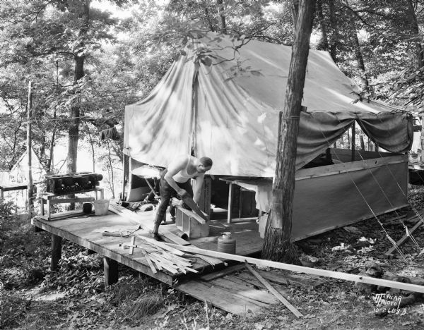 Man sawing wood in front of a tent in the woods at the University of Wisconsin Tent Colony. The tent is set up on a wood platform. Also known as Camp Gallistella on the south shore of Lake Mendota, west of second point.