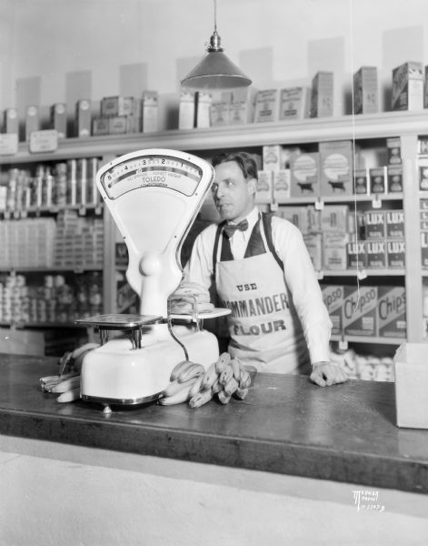 Interior view of a Toledo Computogram scale on a counter in a Dodgeville store, with the grocer weighing bananas. In the background is a display of merchandise on shelves.