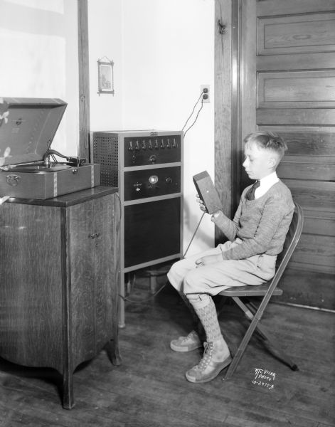 Ben Park, sitting in a chair, is talking to all the classrooms in Lapham school through the radio microphone in the office of Shirley D. Almy, principal. The school is located at 1436 E. Dayton Street.