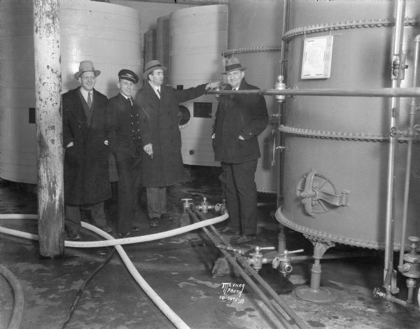 Four men are standing in the tank room at Fauerbach Brewing Co. One of the men is turning a valve. The photograph was taken to mark the modification of the Volstead Act which allowed for the legal sale of beer which began three days later.