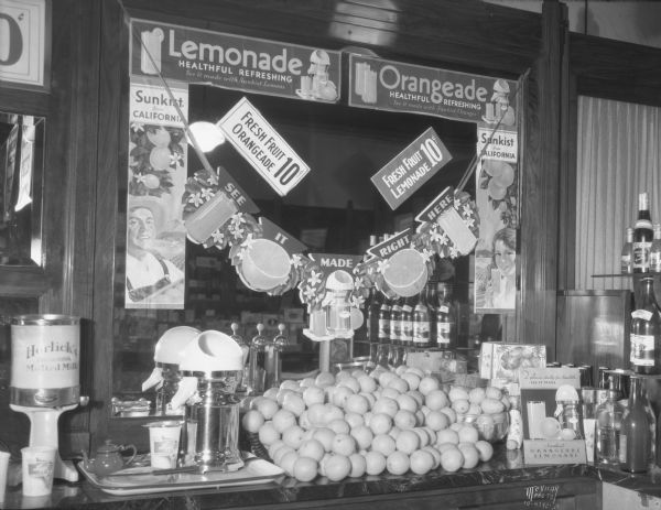 "Ligget's Drug Store at 29 S. Pinckney Street, with a lemonade display on the soda fountain. The signs on the mirror read: ""Lemonade healthful, refreshing,"" ""Orangeade, healthful, refreshing."" On the far left is a can of Horlick's, The Original Malted Milk, on a dispenser."