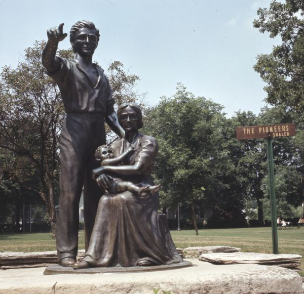 "Bronze statue of a standing man pointing off into the distance, with his wife sitting beside him holding a baby in her lap. The statue sits on a stone platform. A small sign behind the statue reads: ""The Pioneers, Shaler."""