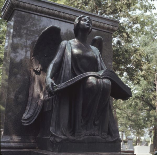 A bronze statue of a female angel holding a large book in her lap is in front of a marble gravestone. Gravestones are in the background on the right.