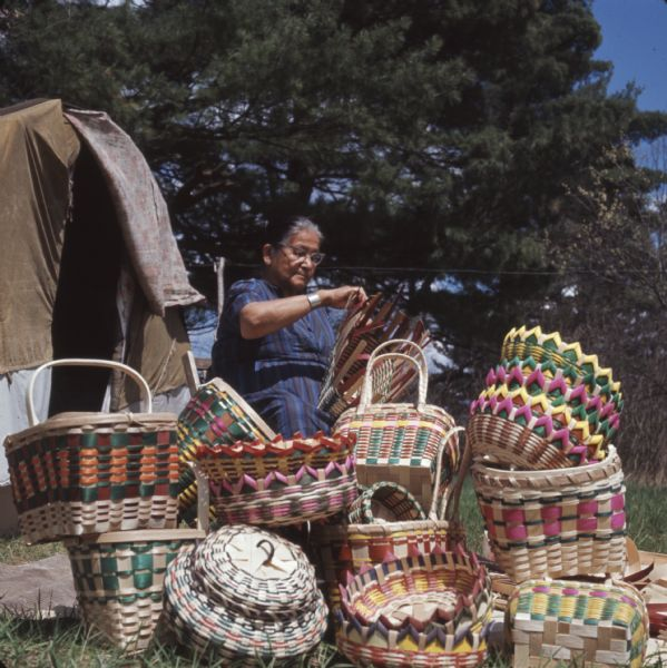 A Ho-Chunk woman, Mable Davis (maiden name) Lowe is sitting and weaving a basket. Behind her is a dwelling (chipoteke). Several finished woven baskets are displayed in front of her.