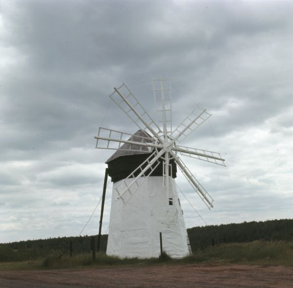 View of a white and green windmill with eight blades is surrounded by a small fence in a rural area. Trees are in the far background.