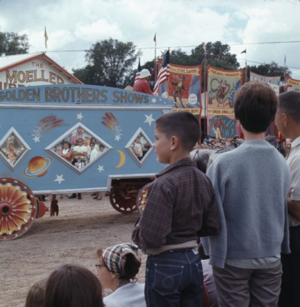 "View from rear of a crowd of people watching circus wagons passing by on a dirt road at Circus World Museum. Two horses are pulling a blue wagon with red and orange wheels with the words ""Golden Brothers Shows"" painted at the top of the wagon. Large banners advertising circus acts are hanging in the background."