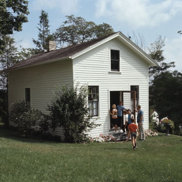 View across lawn towards a man holding open a door for a group of children. They are entering a small white building, the site of America's first kindergarten.