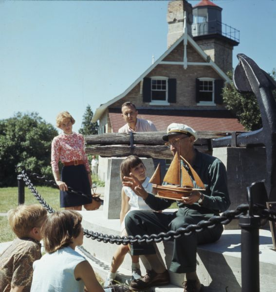 Three children and two adults are stand and sitting around an elderly man wearing a ship captains hat. He is holding a wooden model of a ship. The group of people is gathered around stone pedestal supporting a large anchor. In the background is the Eagle Bluff Lighthouse.