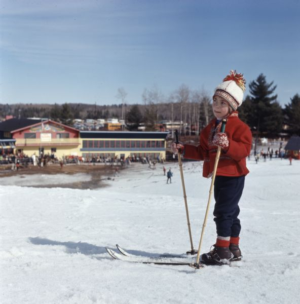 A young child, wearing a Scandinavian style hat, coat, and gloves, is wearing a pair of skis and standing on a small hill. Below the hill in the background is a crowd of people standing outside of the Telemark Lodge.