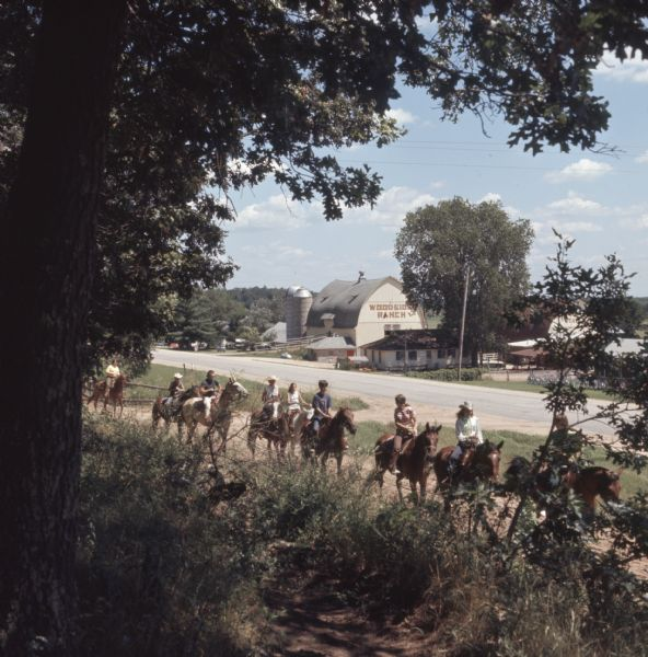View from shade of trees towards a line of teenagers and adults riding horses along a dirt path. Across the road in the background are the barns and stables of Woodside Ranch.