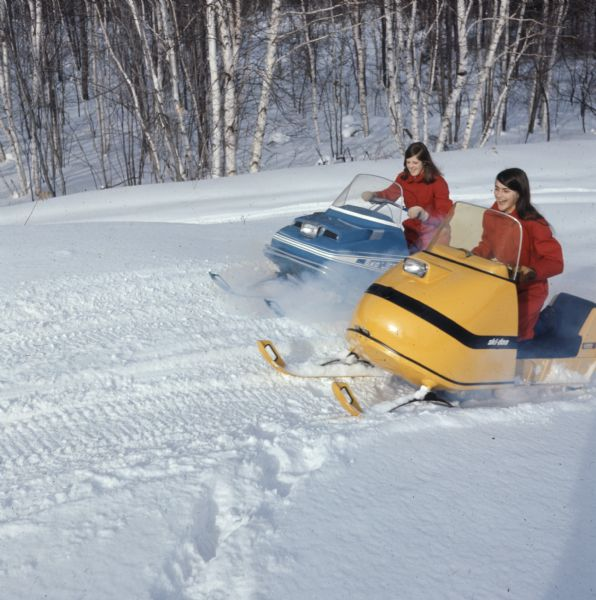 Two women are snowmobiling next to a forested area.