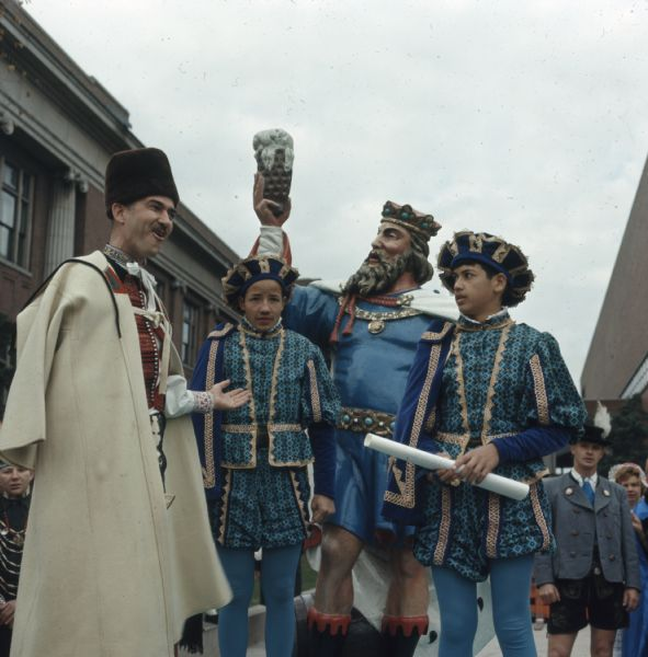 A man wearing Medieval European clothing is gesturing towards a statue of King Gambrinus on a parade float at the Holiday Folk Fair. Two boys, in matching Medieval European outfits, are standing on either side of the statue. One boy is holding a scroll. Other people in various ethnic dress are standing around the float.