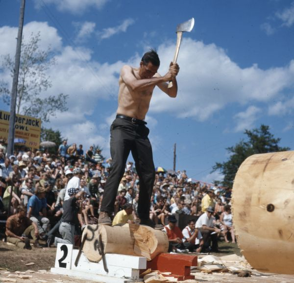 A shirtless man is standing on top of a log ready to chop a log with an axe. A crowd of people are watching from stands behind him.