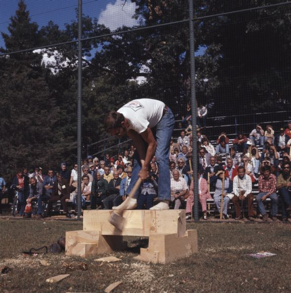 A man is standing on top of a braced wood block. He is bending over as he swings his ax at the wood block on which he is standing. A crowd of people are watching from the stands behind him.