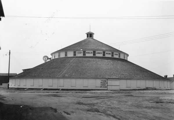 "A large round barn, built as a show barn and arena, standing on the grounds of the Central Wisconsin State Fair. The barn has a band of clerestory windows and a cupola. A windmill is behind the barn on the left. Painted on the barn are signs: ""F.A. Felhofer Designed Erected,"" ""World's Largest Round Barn,"" and ""Farm Products Exhibit Up-Stairs."""