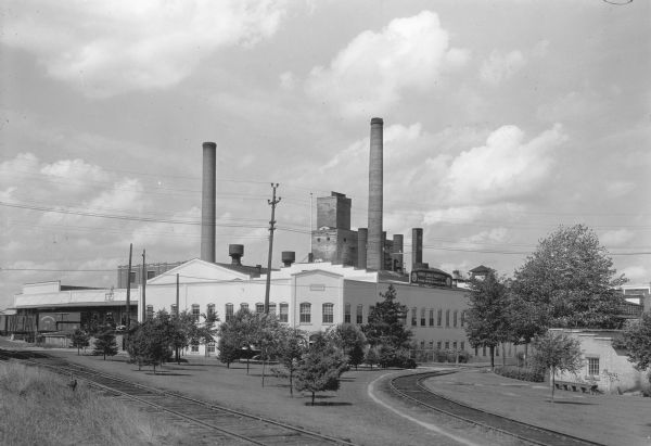"Two large smokestacks rise from the 1903 building of the Rhinelander Paper Company. Railroad tracks are crossing the left foreground diagonally; a second set of tracks are curving off to the right. A sign on the roof at the right side of the building reads: ""Rhinelander Paper Co. Manufacturors of Glassine and Greaseproof Papers."" There are rail cars at the loading docks on the left."