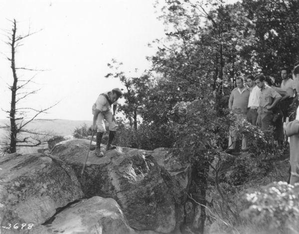 A male guide on the left is using a walking stick to point out a feature in the rocks atop a bluff at Devil's Lake State Park, as a group of men on the right are looking on. The guide is wearing knee-high lace-up boots.