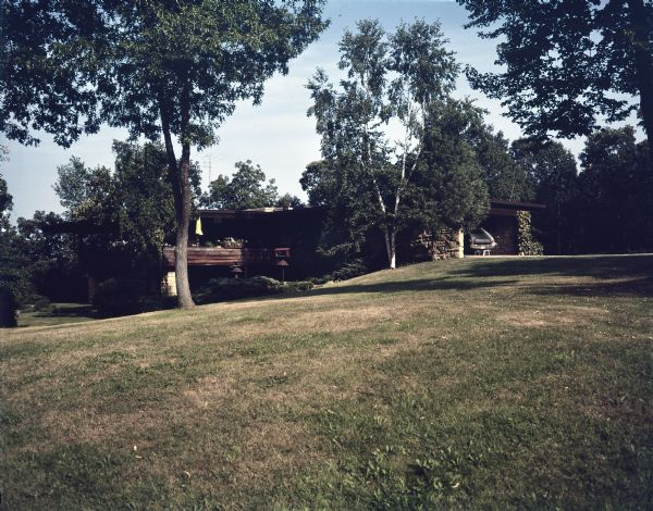 External view across sloping lawn towards a mid-century modern home located by Lake Wisconsin. On the right is a carport framed by stone walls; on the left is an upper and lower level with balcony access, where a closed yellow umbrella stands. There are birdhouses near the balcony, and a tall television antenna is on the roof. The property has a sprawling lawn with trees and garden beds close to the foundation.   The home was built in 1963 and designed by the architect, Paul A. Thomas III, who taught in the Architecture and City and Regional Planning program at Illinois Institute of Technology. Ken Harley was the original owner from 1963 to 1975.
