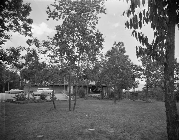 External view across lawn towards the entrance, parking area and lanai of a mid-century modern home by Lake Wisconsin. The lake and a small island are visible through the trees in the distance. The foreground is a long view of the yard with several stands of trees and a couple stumps, cut at ground level. In the middle is the house, where a man in a white shirt is standing under the open-sided varanda, and a parking area with three automobiles — a suburban, a single-door Pontiac coupe and a two-door Chevrolet Impala.   The home was built in 1963 and designed by the architect, Paul A. Thomas III, who taught in the Architecture and City and Regional Planning program at Illinois Institute of Technology. Ken Harley was the original owner from 1963 to 1975.