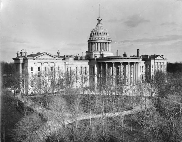 The expanded third Wisconsin State Capitol photographed at a time of the year when the trees in the park did not obstruct the view. As a result, the curvilinear walkways are also clearly visible. The Capitol Park was designed by noted landscape architect Horace W.S. Cleveland, but his design was only partially developed. This photograph is oriented with the North Wing addition at the left.