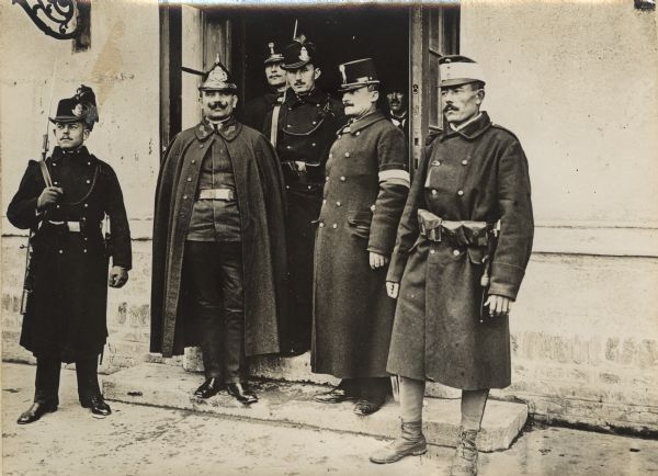 Austrian gendarmes and other officials standing outside a train depot  entrance in Serbia during World War I.