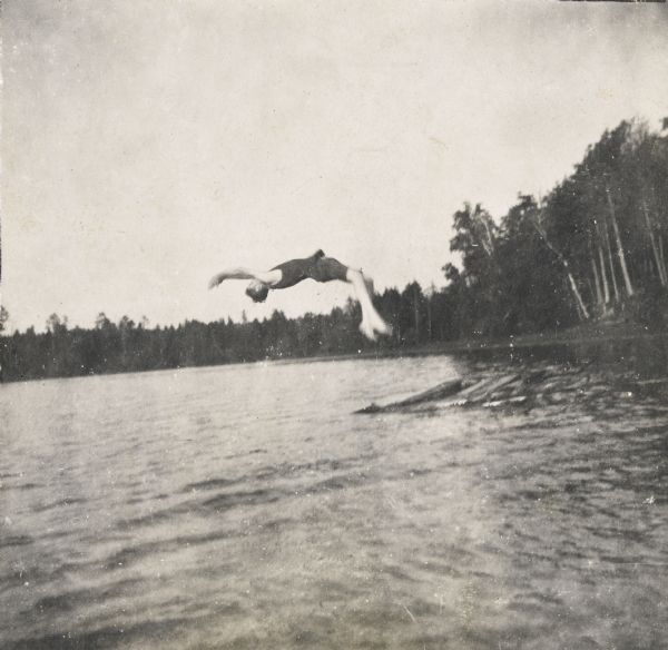 "Wallace Rumsey is doing a back flip dive off a raft into Archibald Lake. Trees and a shoreline are in the background. Photo album page heading reads: ""The recreations of Uncle Wallace."""