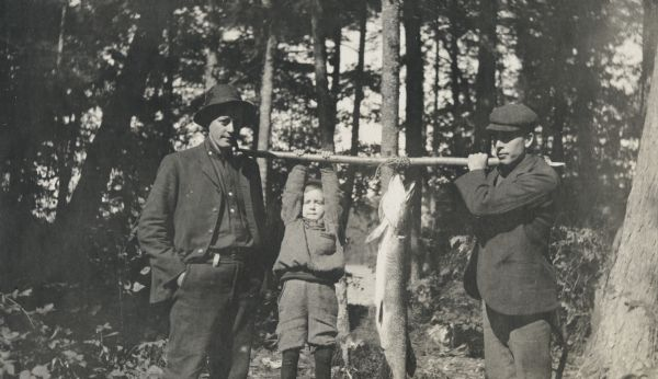 "At Maiden Lake, Dr. Hoover (left) and Rev. John Robertson Macartney (right) are holding a pole with a large pickeral, the size of a boy, hanging from it. Page heading reads: ""Rev. J. Robertson Macartney, Pickeral, Maiden Lake 1903."" Caption below reads: ""Dr. Hoover."""