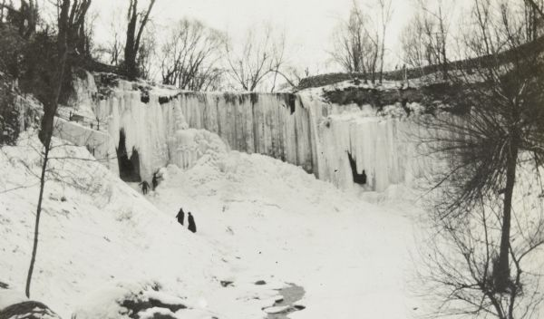 View towards four people walking up to the frozen Minnehaha Falls in Minnehaha Park.