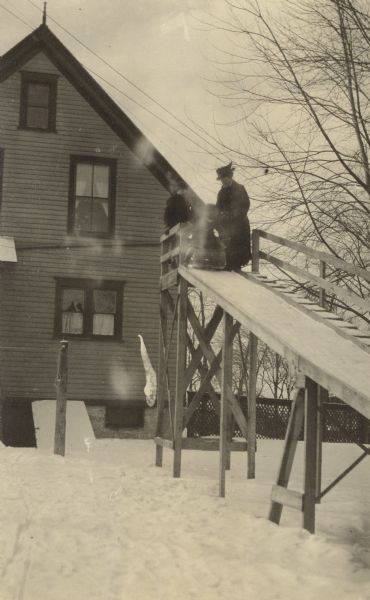 "Atop the winter slide, Lillian Wheeler is positioning herself on the sled. Her mother Anna Holt Wheeler is watching her, and a third person is standing behind the sled. There is a house in the background and snow is on the ground. Caption reads: ""Mrs. Wheeler and Lillian."""