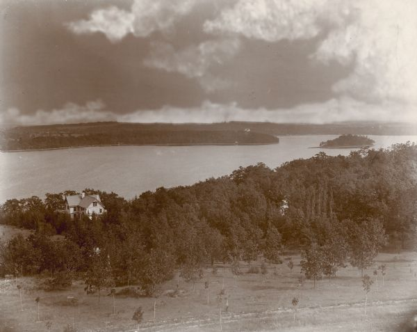 An elevated view of Pine Lake and the George Brumder summer house, taken from an observation tower built on a hill on the Brumder property. Many young trees have been planted in the foreground. The water storage tank for the house is visible through the trees near the house. Obscured by trees at the right is a glimpse of the caretaker's house.