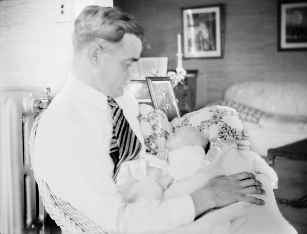 Herbert Paul Brumder, sitting in a wicker chair, is holding his infant son, Herbert Edmund Brumder. There is a steam radiator on the left.