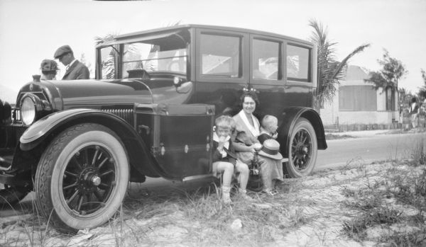 Margaret (Mrs. Herbert Paul) Brumder is sitting on the running board of a well-polished automobile with her two sons, Herbert Edmund, left, and Philip George. The front porch of a small bungalow is seen across the road on the right. There is an unidentified couple behind the car at left. Two young palm trees are in the background behind the car.